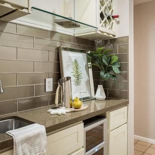 他の地域の小さいトランジショナルスタイルのおしゃれなウェット バー (I型、アンダーカウンターシンク、シェーカースタイル扉のキャビネット、白いキャビネット、クオーツストーンカウンター、グレーのキッチンパネル、ガラスタイルのキッチンパネル、テラコッタタイルの床、ベージュの床) の写真