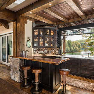 Large mountain style brown floor and dark wood floor seated home bar photo in Other with an undermount sink, glass-front cabinets, brown cabinets, metal backsplash and white countertops
