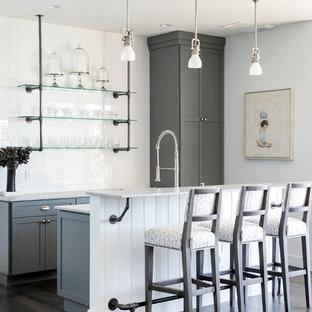 他の地域の中くらいのカントリー風おしゃれなウェット バー (ll型、アンダーカウンターシンク、フラットパネル扉のキャビネット、グレーのキャビネット、クオーツストーンカウンター、白いキッチンパネル、セメントタイルのキッチンパネル、濃色無垢フローリング、茶色い床、白いキッチンカウンター) の写真