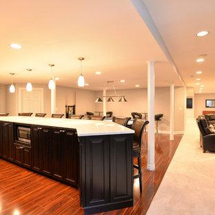 シカゴの中くらいのモダンスタイルのおしゃれなウェット バー (L型、アンダーカウンターシンク、レイズドパネル扉のキャビネット、黒いキャビネット、無垢フローリング、茶色い床、白いキッチンカウンター) の写真