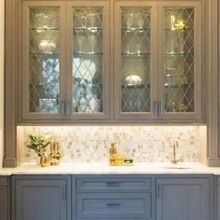 シカゴの中くらいのトランジショナルスタイルのおしゃれなウェット バー (I型、アンダーカウンターシンク、落し込みパネル扉のキャビネット、グレーのキャビネット、珪岩カウンター、黄色いキッチンパネル、ガラス板のキッチンパネル、濃色無垢フローリング、茶色い床、白いキッチンカウンター) の写真