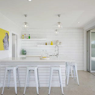 Design ideas for a beach style galley seated home bar in Other with an undermount sink, white splashback, white benchtop and grey floor.