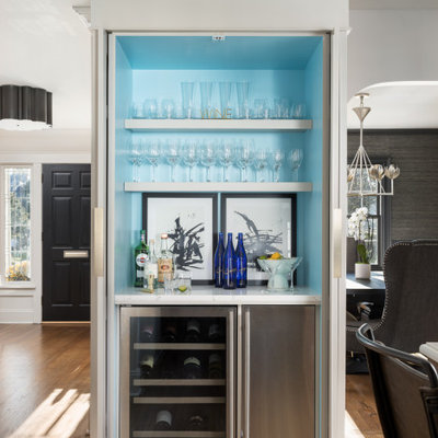 Example of a small transitional single-wall medium tone wood floor and brown floor seated home bar design in New York with a drop-in sink, white cabinets, quartz countertops, white backsplash, marble backsplash, white countertops and open cabinets