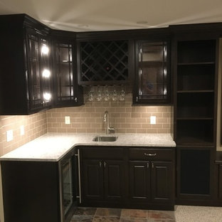 Small transitional l-shaped beige floor home bar photo in Other with an undermount sink, glass-front cabinets, black cabinets and beige backsplash
