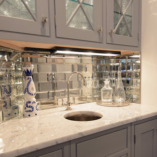 This is an example of a small classic single-wall wet bar in New York with a submerged sink, glass-front cabinets, grey cabinets, marble worktops, metro tiled splashback and dark hardwood flooring.