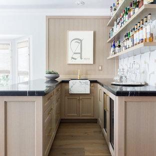 Immagine di un bancone bar classico con lavello sottopiano, ante in stile shaker, paraspruzzi bianco, parquet chiaro e top nero