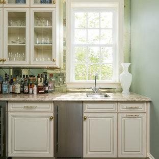 Immagine di un grande bancone bar tradizionale con lavello sottopiano, ante con bugna sagomata, ante bianche, top in granito, paraspruzzi a specchio, parquet scuro e pavimento marrone