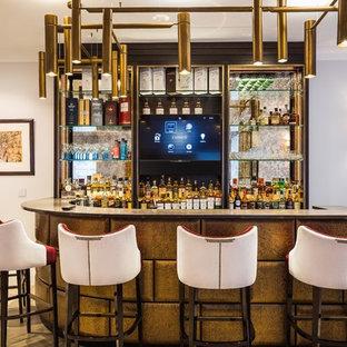 Inspiration for a medium sized classic single-wall breakfast bar in London with open cabinets, mirror splashback, light hardwood flooring, beige floors and black worktops.