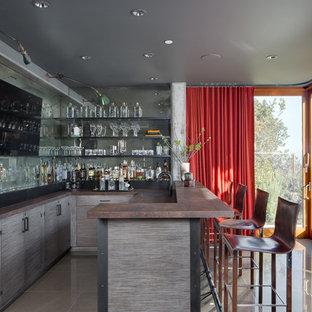 サンフランシスコの広いコンテンポラリースタイルのおしゃれな着席型バー (ミラータイルのキッチンパネル、グレーの床、L型、アンダーカウンターシンク、フラットパネル扉のキャビネット、グレーのキャビネット) の写真