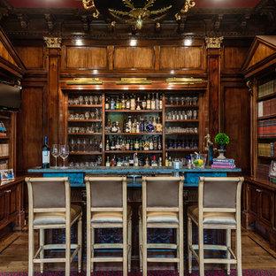 ダラスのトラディショナルスタイルのおしゃれなウェット バー (アンダーカウンターシンク、オープンシェルフ、濃色木目調キャビネット、無垢フローリング、茶色い床、青いキッチンカウンター) の写真