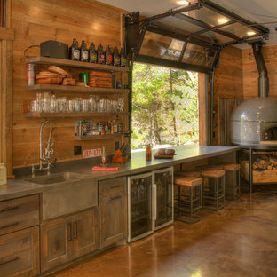 Example of a mountain style single-wall concrete floor and brown floor home bar design in Minneapolis with an integrated sink, shaker cabinets, dark wood cabinets and gray countertops
