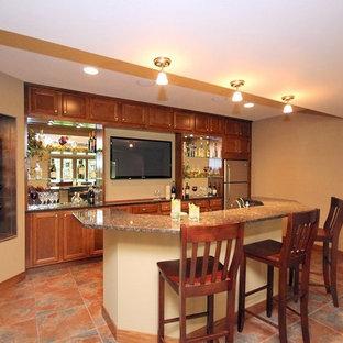 他の地域の広いトラディショナルスタイルのおしゃれな着席型バー (アンダーカウンターシンク、セラミックタイルの床、ll型、落し込みパネル扉のキャビネット、中間色木目調キャビネット、御影石カウンター、グレーのキッチンパネル、ミラータイルのキッチンパネル、赤い床) の写真