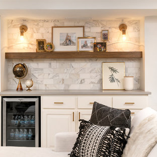 Design ideas for a medium sized classic single-wall home bar in Milwaukee with no sink, raised-panel cabinets, white cabinets, engineered stone countertops, white splashback, metro tiled splashback, laminate floors, brown floors and grey worktops.