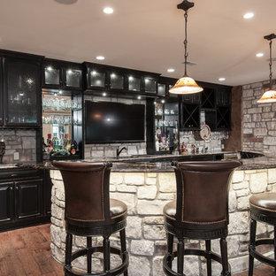 セントルイスの広いラスティックスタイルのおしゃれな着席型バー (I型、アンダーカウンターシンク、レイズドパネル扉のキャビネット、黒いキャビネット、御影石カウンター、グレーのキッチンパネル、石タイルのキッチンパネル、無垢フローリング、茶色い床) の写真
