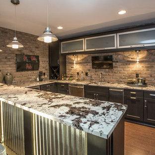 Immagine di un angolo bar con lavandino minimalista di medie dimensioni con lavello sottopiano, ante di vetro, ante nere, top in granito, paraspruzzi beige, pavimento in sughero e paraspruzzi in mattoni