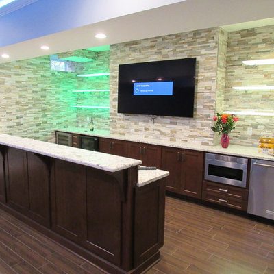 Large trendy galley porcelain tile wet bar photo in New York with shaker cabinets, dark wood cabinets, granite countertops, multicolored backsplash, stone tile backsplash and an undermount sink