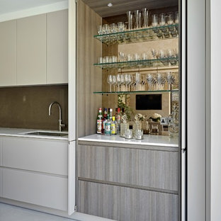 Photo of a contemporary single-wall wet bar in London with a submerged sink, flat-panel cabinets, grey cabinets, mirror splashback, grey floors and white worktops.