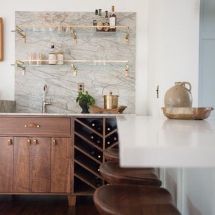 ロサンゼルスの中くらいのコンテンポラリースタイルのおしゃれなウェット バー (I型、アンダーカウンターシンク、フラットパネル扉のキャビネット、中間色木目調キャビネット、大理石カウンター、グレーのキッチンパネル、石スラブのキッチンパネル、濃色無垢フローリング、グレーのキッチンカウンター) の写真