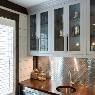 シンシナティの中くらいのトラディショナルスタイルのおしゃれなウェット バー (アンダーカウンターシンク、落し込みパネル扉のキャビネット、グレーのキャビネット、木材カウンター、無垢フローリング、グレーのキッチンパネル、メタルタイルのキッチンパネル、茶色い床) の写真
