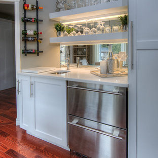 Photo of a small contemporary single-wall wet bar in Toronto with a submerged sink, shaker cabinets, white cabinets, engineered stone countertops, mirror splashback, medium hardwood flooring, brown floors and white worktops.
