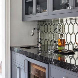 Imagen de bar en casa con fregadero lineal, tradicional, con fregadero bajoencimera, armarios con paneles empotrados, puertas de armario grises, salpicadero con efecto espejo, suelo de madera oscura, suelo marrón y encimeras negras