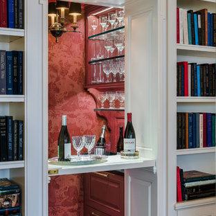 Esempio di un angolo bar vittoriano di medie dimensioni con ante con bugna sagomata, ante rosse e top in granito