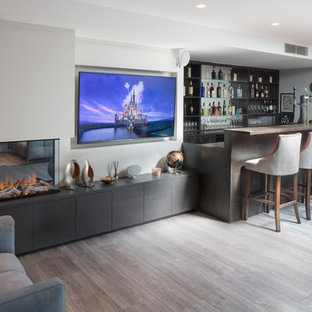 Photo of a medium sized classic single-wall wet bar in London with flat-panel cabinets, black cabinets, grey floors, brown worktops, mirror splashback and vinyl flooring.