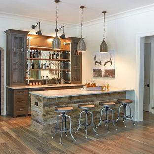 Ispirazione per un ampio angolo bar country con pavimento in legno massello medio