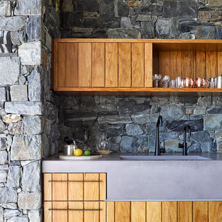 Inspiration for a small country single-wall home bar in Brisbane with an integrated sink, medium wood cabinets, concrete benchtops, grey splashback, stone tile splashback and flat-panel cabinets.