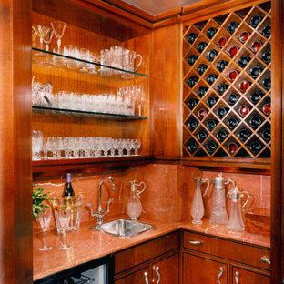 ニューヨークの中くらいのトラディショナルスタイルのおしゃれなウェット バー (L型、ドロップインシンク、フラットパネル扉のキャビネット、濃色木目調キャビネット、オレンジのキッチンパネル、石スラブのキッチンパネル) の写真
