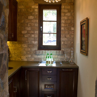 Example of a large mountain style single-wall medium tone wood floor wet bar design in San Francisco with an undermount sink, raised-panel cabinets, dark wood cabinets, solid surface countertops, brown backsplash and brick backsplash