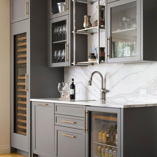 Photo of a classic single-wall wet bar in Calgary with a submerged sink, glass-front cabinets, grey cabinets, white splashback, light hardwood flooring, beige floors, marble worktops, marble splashback and white worktops.