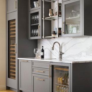 カルガリーのトランジショナルスタイルのおしゃれなウェット バー (I型、アンダーカウンターシンク、ガラス扉のキャビネット、グレーのキャビネット、白いキッチンパネル、淡色無垢フローリング、ベージュの床、大理石カウンター、大理石のキッチンパネル、白いキッチンカウンター) の写真