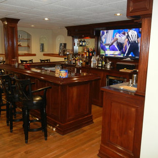 Large elegant l-shaped medium tone wood floor and brown floor wet bar photo in Atlanta with a drop-in sink, recessed-panel cabinets, dark wood cabinets, wood countertops and mirror backsplash