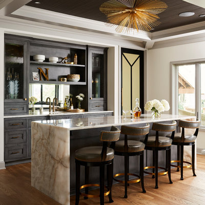 Example of a huge transitional galley medium tone wood floor and brown floor wet bar design in Minneapolis with an undermount sink, recessed-panel cabinets, dark wood cabinets, quartzite countertops, mirror backsplash and white countertops