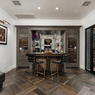 フェニックスの巨大な地中海スタイルのおしゃれな着席型バー (ステンレスカウンター、茶色い床、ll型、ミラータイルのキッチンパネル、無垢フローリング、グレーのキャビネット、オープンシェルフ) の写真
