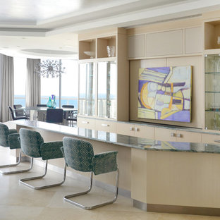 マイアミの巨大なコンテンポラリースタイルのおしゃれな着席型バー (ライムストーンの床、ガラス扉のキャビネット、淡色木目調キャビネット、ベージュの床、緑のキッチンカウンター) の写真