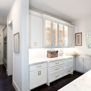 Aménagement d'un très grand bar de salon avec évier classique en U avec un placard à porte vitrée, des portes de placard blanches, un plan de travail en marbre, une crédence blanche et un plan de travail blanc.