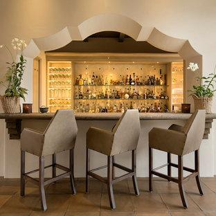 サンタバーバラの地中海スタイルのおしゃれな着席型バー (ベージュキッチンパネル、セラミックタイルのキッチンパネル、テラコッタタイルの床、オープンシェルフ) の写真