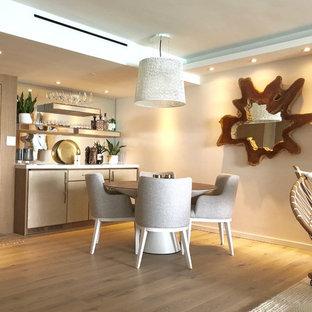 マイアミの中くらいのモダンスタイルのおしゃれなホームバー (I型、シンクなし、フラットパネル扉のキャビネット、ベージュのキャビネット、大理石カウンター、ミラータイルのキッチンパネル、淡色無垢フローリング、ベージュの床) の写真