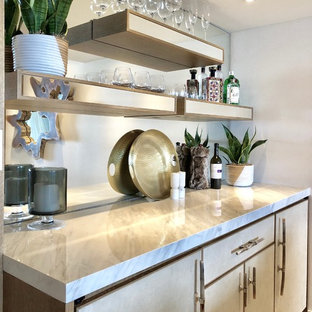This is an example of a medium sized modern single-wall wet bar in Miami with no sink, flat-panel cabinets, beige cabinets, marble worktops, mirror splashback, light hardwood flooring and beige floors.