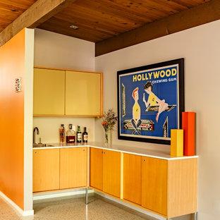 ポートランドの中くらいのミッドセンチュリースタイルのおしゃれなウェット バー (L型、フラットパネル扉のキャビネット、ベージュの床、淡色木目調キャビネット、アンダーカウンターシンク、コンクリートの床、白いキッチンカウンター) の写真