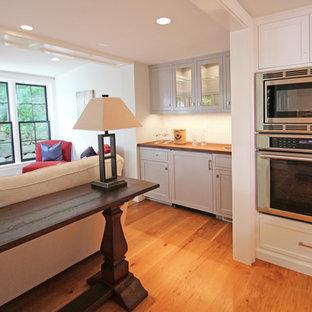 ボストンの小さいトランジショナルスタイルのおしゃれなウェット バー (I型、ドロップインシンク、シェーカースタイル扉のキャビネット、グレーのキャビネット、木材カウンター、白いキッチンパネル、サブウェイタイルのキッチンパネル、濃色無垢フローリング、茶色い床) の写真