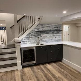 ボストンの中くらいのトランジショナルスタイルのおしゃれなウェット バー (L型、アンダーカウンターシンク、グレーのキャビネット、人工大理石カウンター、グレーのキッチンパネル、石タイルのキッチンパネル、無垢フローリング、茶色い床、白いキッチンカウンター) の写真