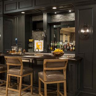 ミネアポリスのトランジショナルスタイルのおしゃれな着席型バー (レンガの床、ll型、落し込みパネル扉のキャビネット、黒いキャビネット、木材カウンター、グレーのキッチンパネル、石タイルのキッチンパネル、ベージュの床、茶色いキッチンカウンター) の写真