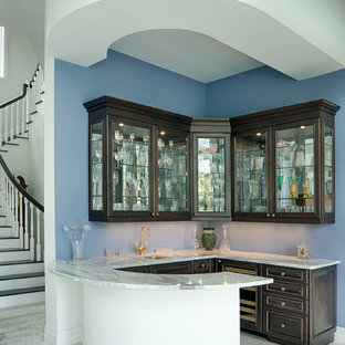 Inspiration for a traditional home bar in Miami with raised-panel cabinets and marble worktops.