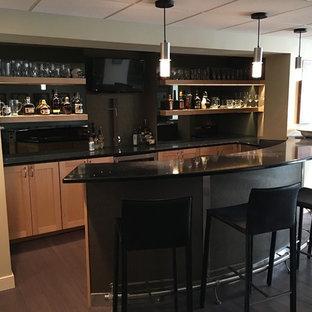 フィラデルフィアの広いモダンスタイルのおしゃれな着席型バー (コの字型、シェーカースタイル扉のキャビネット、淡色木目調キャビネット、人工大理石カウンター、黒いキッチンパネル、濃色無垢フローリング、茶色い床、黒いキッチンカウンター) の写真