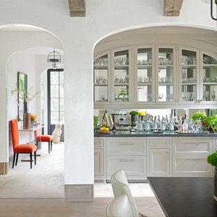 Ispirazione per un piccolo angolo bar con lavandino chic con lavello sottopiano, ante in stile shaker, ante bianche, paraspruzzi a specchio e pavimento in travertino