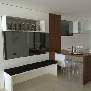 This is an example of a medium sized contemporary single-wall wet bar in Dorset with flat-panel cabinets, white cabinets, wood worktops, white splashback, glass sheet splashback and ceramic flooring.