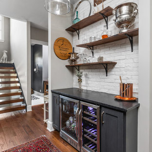 Inspiration for a small farmhouse single-wall home bar in Indianapolis with no sink, shaker cabinets, black cabinets, white splashback, brick splashback, dark hardwood flooring and black worktops.
